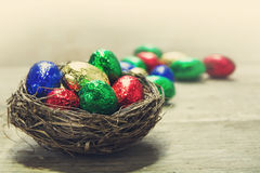 Retro chocolate easter eggs in a nest on a rustic wooden table,. Colorful chocolate easter eggs in a nest on a rustic wooden table, some blurred eggs in the stock photo