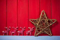 Retro Christmas star and reindeer on red wood background Stock Photography