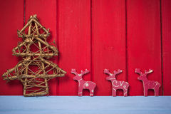 Retro Christmas tree and reindeer on red wood background Royalty Free Stock Photography