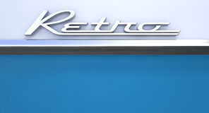 Retro Chrome Car Emblem. A closeup view of the word retro writting as a chrome emblem in a retro font set on a car painted in two tones of white and blue royalty free stock photo