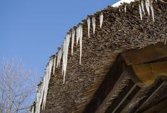 Retro cielo blu del fondo del tetto della paglia dei piccoli ghiaccioli Fotografie Stock