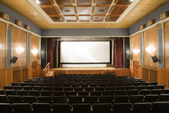Retro cinema. Empty old retro style cinema auditorium with line of chairs and stage with silver screen. Ready for adding your own picture Stock Image