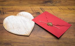 Retro classic Valentine`s Day cad, large white painted wooden hart, isolated, red envelope with wax seal, on vintage oak panels - royalty free stock photography