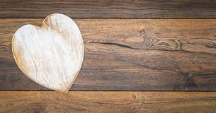 Retro classic Valentine`s Day cad, large white painted wooden hart isolated and on left side with large copy space on vintage oak royalty free stock image