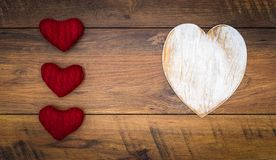 Retro classic Valentine`s Day cad, large white painted wooden hart, isolated, 3 red cuddle harts, on vintage oak panels - top view stock image