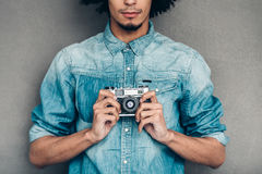 Retro click. Close-up part of young African man in jeans shirt holding retro styled camera while standing against grey background stock photos