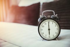 Retro clock on bad morning wake up times 6 o`clock. In the bedroom stock photo