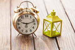 Retro  clock and decorate lamp on wooden table. Royalty Free Stock Image