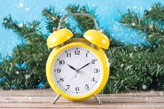 Retro clock on desk and Christmas fir tree in background stock photography