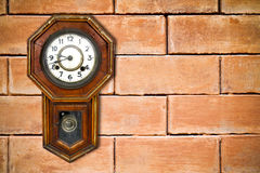 Retro clock hanging on brick wall Royalty Free Stock Photo