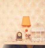 Retro clock, lamp and birdcage backdrop. Stock Photos
