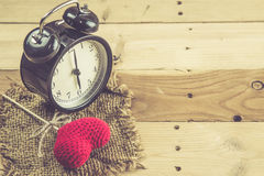 Retro clock with love heart yarn on wood stick on wood background Stock Images