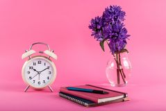 Blog concept image with old clock, notebooks and flowers in a vase on a pink background. Retro clock, pen on notebook and purple flower in vase on pink stock photo