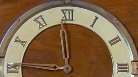 Retro clock with Roman numerals. Close up view of a half face of antique wooden clock with Roman numerals showing time approaching 12 midday or midnight stock footage