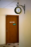 Retro Clock on the wall. Waiting lobby with retro victorian clock on the wall and brown doors behind Stock Photos