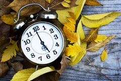 Retro clock on a wooden table with autumn leaves Royalty Free Stock Photo