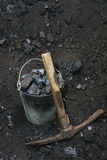 Retro coal mining. Pickaxe and the bucket full of lumps of coal Royalty Free Stock Photography