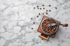 Retro coffee grinder with beans. On marble background, top view Royalty Free Stock Photography