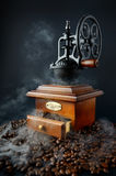 Retro coffee grinder with beans and smoke isolated on black Royalty Free Stock Photo