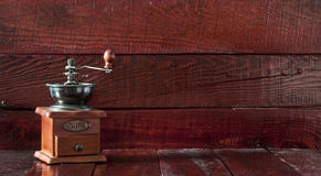 Retro coffee grinder. On old table and textured wood background Stock Photography