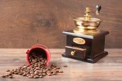 Retro coffieemolar- och kaffebönor på brun bakgrund arkivbild