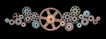 Retro Cogs Gears Technology. Various old cogs and gears of different colours and sizes in a cloud like formation on a black background stock photography