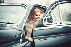 Retro collection car and auto repair by driver. sexy woman in fur coat. Travel and business trip or hitch hiking. Escort. And security guard for luxury woman royalty free stock photos
