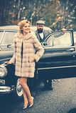 Retro collection car and auto repair by mechanic driver. Bearded man and sexy woman in fur coat. Escort of girl by. Retro collection car and auto repair by royalty free stock photos