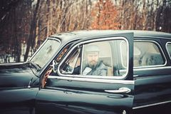 Retro collection car and auto repair by mechanic driver. Bearded man and sexy woman in car. Travel and business trip or. Retro collection car and auto repair by stock photography