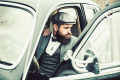 Retro collection car and auto repair by mechanic driver. Travel and business trip or hitch hiking. Escort of girl by. Security. Bearded man and sexy woman in stock photo