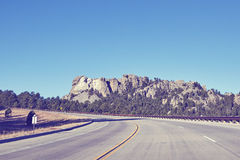 Retro color toned road to Mount Rushmore National Memorial, USA. Royalty Free Stock Images