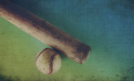 Retro coloring of old baseball bat and ball. Old wooden bat showing grains laying beside vintage ball.  Sports equipment in retro color setting, great for Royalty Free Stock Photo