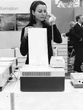 Retro communication. Girl is using an old telephone and a fax at the same time Stock Images