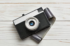 Retro compact photo camera and film on white Royalty Free Stock Photo