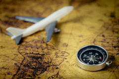 Retro Compass with airplane on Vintage world map for explorer concept. Retro Compass with toy airplane on Vintage world map for explorer concept Royalty Free Stock Photos