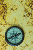 Retro compass on antique world map Stock Images