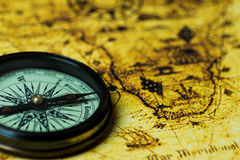 retro compass on antique world map Stock Photos