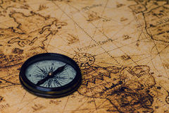 Retro compass on antique world map Royalty Free Stock Photos