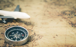 Retro Compass with toy airplane on Vintage world map. For explorer concept with copy space Royalty Free Stock Photos