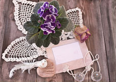 Retro composition with photo frame, knitted napkins and viola Stock Photos