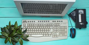 Retro computer on blue wooden table. Monitor, keyboard, pc mouse, pot with plant, video cassette top view. Retro computer on blue wooden table. Monitor stock images