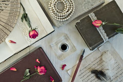 Retro concept with book and beads. Old book and dry rose and accessories for writing. Retro concept Stock Photo