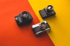 Retro concetto di tecnologia di creatività Macchine da presa su fondo rosso ed arancio, vista superiore Immagine Stock