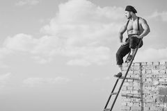 Retro construction worker climbing a ladder while working on the royalty free stock photo