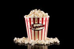 Retro contenitore di popcorn in pieno e popcorn rovesciato isolato sul nero fotografia stock libera da diritti