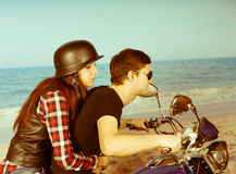 Retro couple riding a motorbike on the beach Royalty Free Stock Photo
