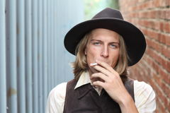 Retro cowboy smoking cigarette. Young man Stock Images