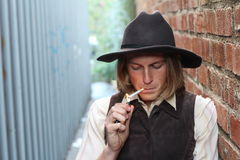 Retro cowboy smoking cigarette. Young man lighting a cigarette Royalty Free Stock Images