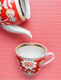 Retro cup and teapot with red patterns on tablecloth with polka dots. Top view. Retro cup and teapot with red patterns on tablecloth with polka dots. Top view stock image