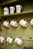 Retro cups. Hanging on wooden wall Royalty Free Stock Images